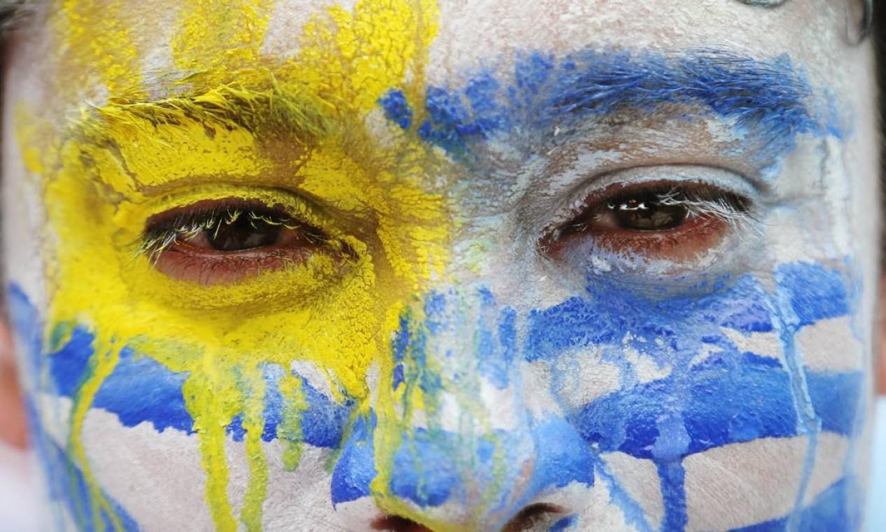 Uruguaio exibe a paixão pelo país no rosto Foto: Petr David Josek / AP
