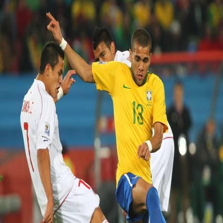 Daniel Alves divide a bola com Alexis Sánchez na goleada de 4 a 0 do Brasil sobre o Chile nas oitavas de final da Copa de 2010 Foto: Ivo Gonzalez/28-6-2010