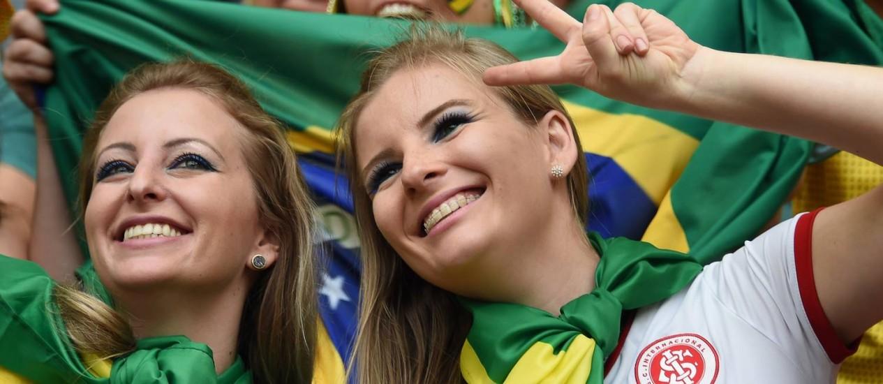 Brasileiras torcem para a seleção durante jogo contra Camarões no estádio Mané Garrincha, em Brasília Foto: VANDERLEI ALMEIDA / AFP
