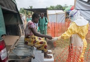 Aperto de mão. Contato físico só é permitido mediante o uso do traje especial de proteção. Foto: Sylvain Cherkaoui/MSF