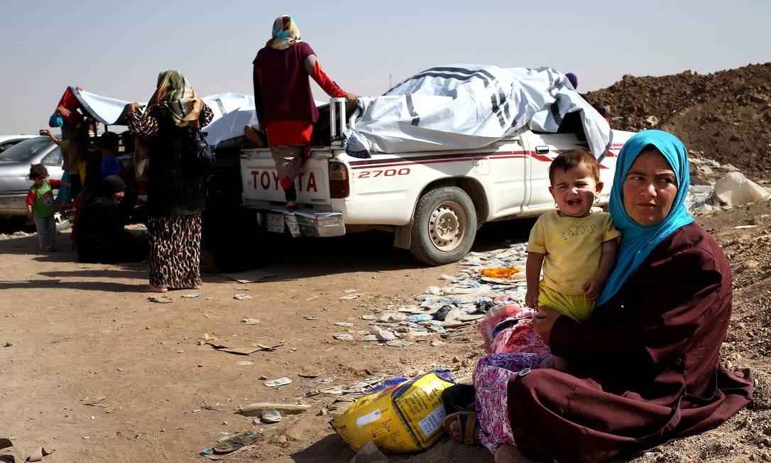 Iraquianos que fugiram da violência de insurgentes esperam ajuda das forças de segurança curdas durante a noite em um posto de controle na área de Khazer Foto: Hussein Malla / AP