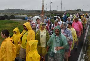 Torcedores usam capas de chuva na chagada à Arena Pernambuco Foto: Nelson Almeida / AFP