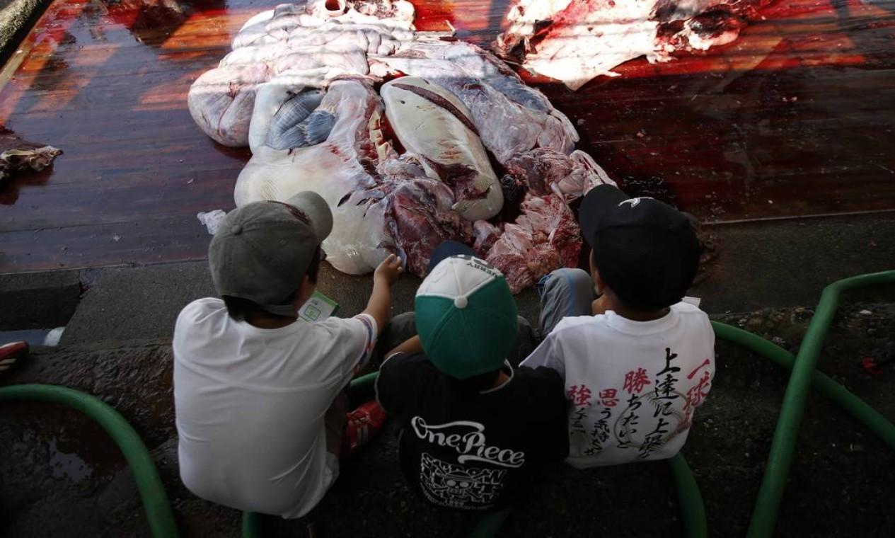 Crianças observam entranhas de animais mortos Foto: ISSEI KATO / REUTERS