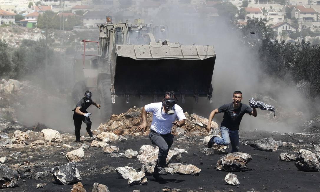 Manifestantes palestinos fogem de um trator israelense na Cisjordânia Foto: MOHAMAD TOROKMAN / Reuters
