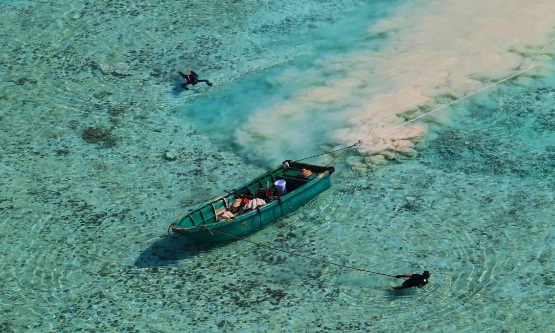 Pescador em meio a corais próximo às Ilhas Paracel, no Sul da China: paraíso ameaçado Foto: Latinstock
