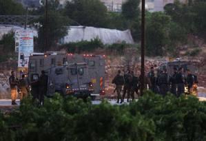 Soldados israelenses patrulham a entrada de Halhul, na Cisjordânia, onde foram encontrados os corpos de 3 adolescentes sequestrados Foto: MENAHEM KAHANA / AFP