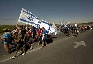 Israelenses marcham na estrada perto de onde três adolescentes desaparecidos foram sequestrados e mortos na Cisjordânia Foto: Sebastian Scheiner / AP
