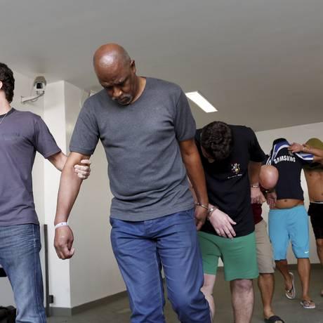 O argelino Mohamadou Lamine é conduzido à frente dos outros detidos na Operação Jules Rimet Foto: Hudson Pontes / Agência O Globo