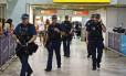 Policiais armados caminham em frente ao portão de desembarque no aeroporto de Heathrow, em Londres, em 23 de julho de 2012