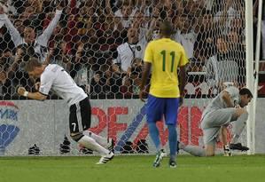 Superioridade. Schweinsteger comemora o gol de pênalti feito contra o Brasil no amistoso de 2011, em Stuttgart; Júlio César e Fernandinho lamentam Foto: THOMAS KIENZLE / AFP