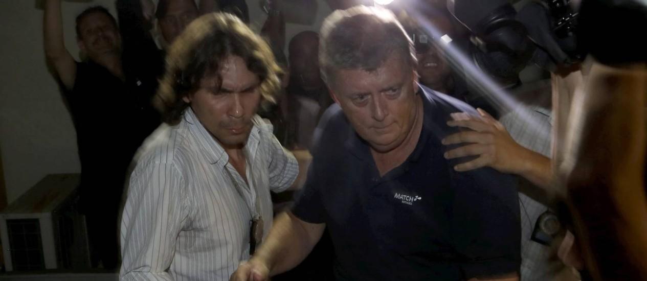 O diretor da Match, Raymond Whelan (de blusa escura), quando foi levado à 18ª DP (Praça da Bandeira) Foto: Hudson Pontes / Agência O Globo