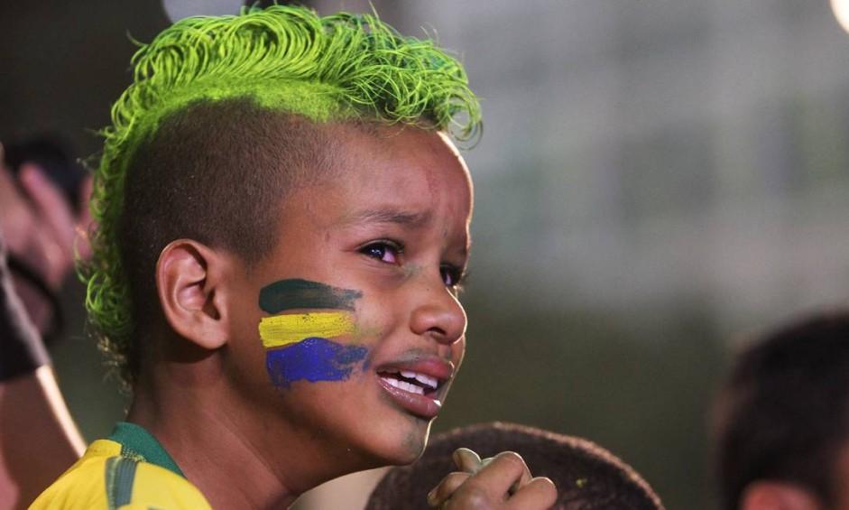 O garoto João Henrique, de oito anos, chora muito ao ver o sétimo gol da Alemanha Foto: Fernando Donasci / Agência O Globo