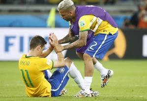 Daniel Alves reconforta Oscar, que chorou muito após a vergonhosa goleada da Alemanha no Brasil, no Mineirão Foto: Ivo Gonzalez