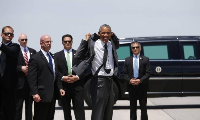 Barack Obama sorri e veste um blazer próximo a agentes do serviço secreto antes de embarcar no Air Force One para usa viagem ao Texas Foto: KEVIN LAMARQUE / REUTERS
