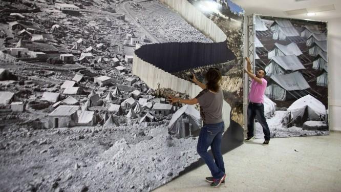 Em Belém (Israel), exposição em um centro comunitário para refugiados da Palestina superpõe imagens recentes e mais antigas de refugiados palestinos separados por barreira israelense Foto: AHMAD GHARABLI / AFP