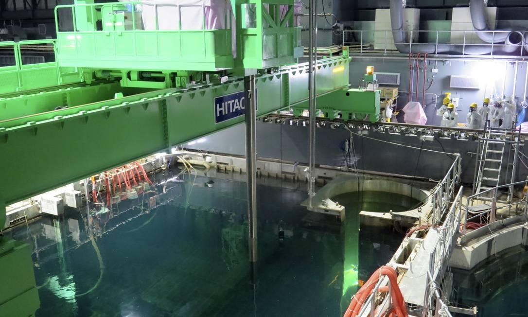 Na imagem de 2013, trabalhadores tentam remover material radioativo liberado após usina de Fukushima ser atingida por tsunami e sofrer uma pane em seus sistemas de resfriamento Foto: / AP