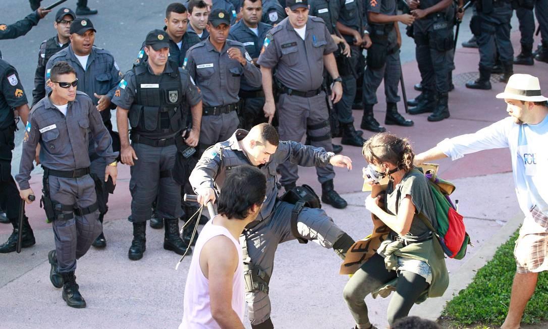 Policial chuta manifestante durante protesto na Saens Peña Foto: Marcelo Piu / Agência O Globo