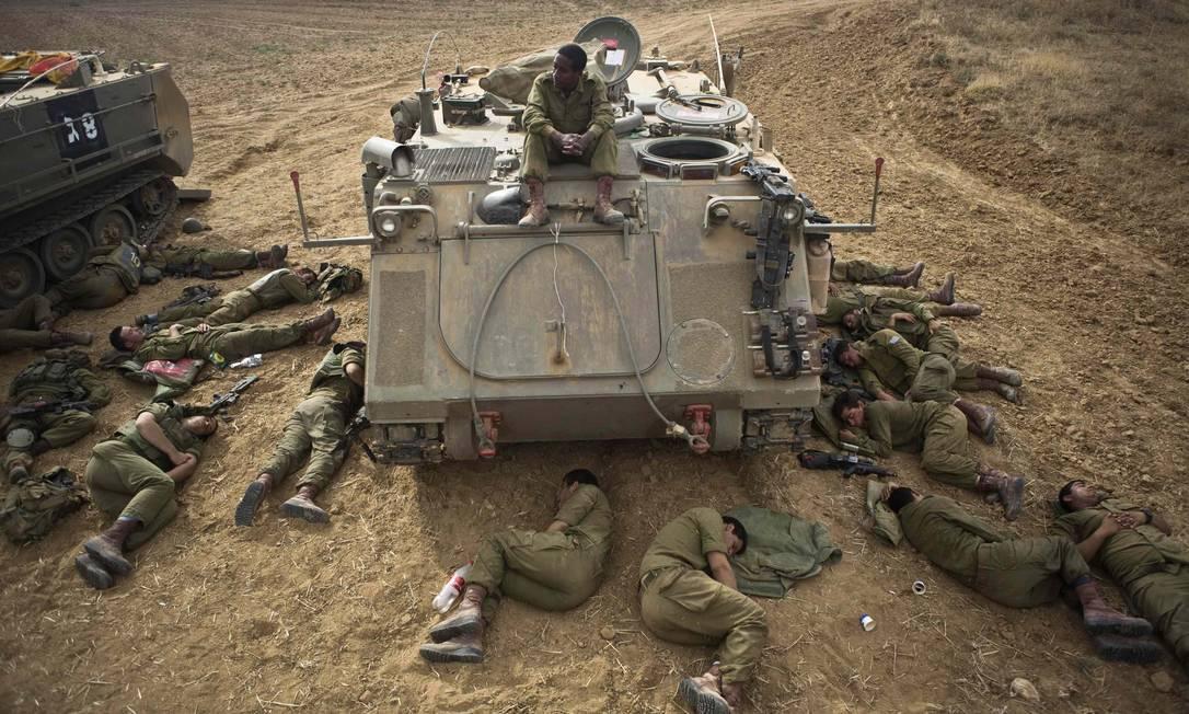 Soldados israelenses dormem no chão ao lado de tanque na fronteira com a Faixa de Gaza Foto: NIR ELIAS / REUTERS