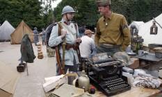 Homens usam uniforme próximo a uma máquina de escrever em uma reconstituição da Primeira Guerra Mundial Foto: THOMAS SAMSON / AFP