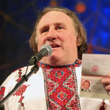 Com roupa típica russa, Depardieu mostra o passaporte entregue pessoalmente por Vladimir Putin Foto: Yulia Chestnova/STRINGER / REUTERS