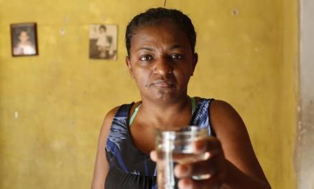 SEM ÁGUA: Embora tenha um hidrômetro, Vanessa Martins não recebe água da rede e sequer tem torneira em casa Foto: Agência O Globo / Simone Marinho