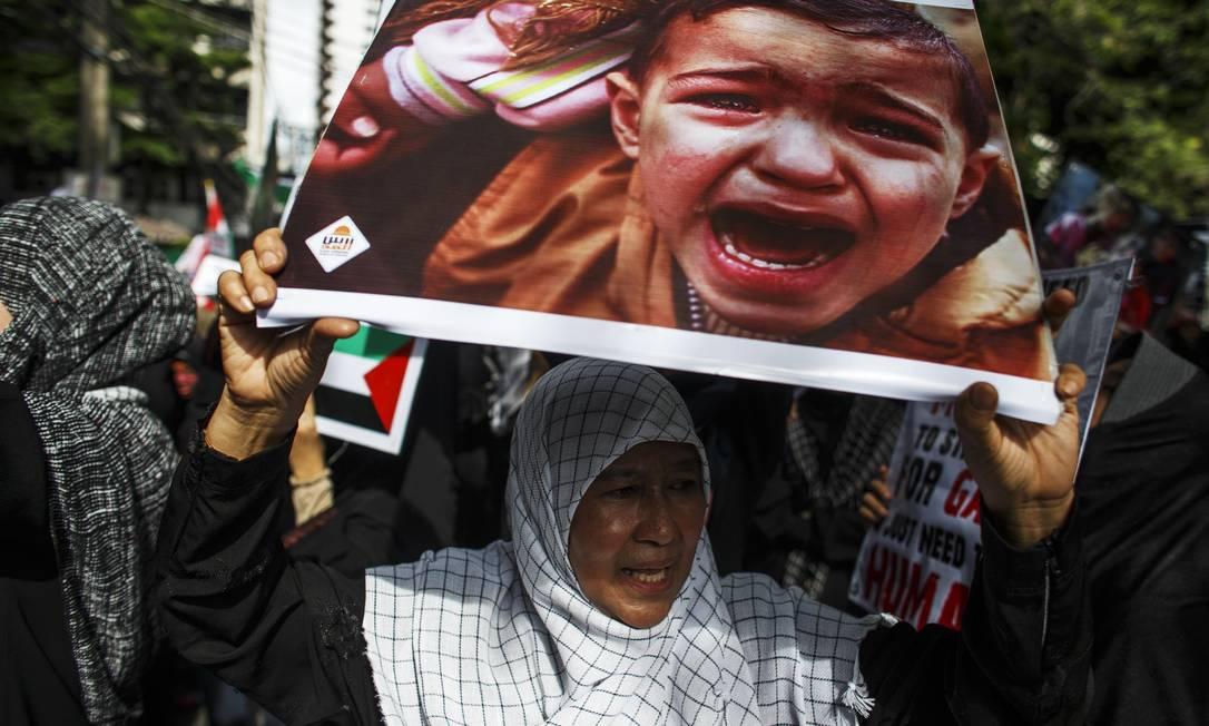 Manifestante segura um cartaz durante um protesto contra Israel em frente à embaixada de Israel em Bangcoc Foto: ATHIT PERAWONGMETHA / Reuters