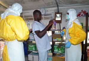 Integrantes do Médicos sem Fronteiras colocam equipamentos de proteção após homem morrer com sintomas de ebola Foto: CELLOU BINANI / AFP