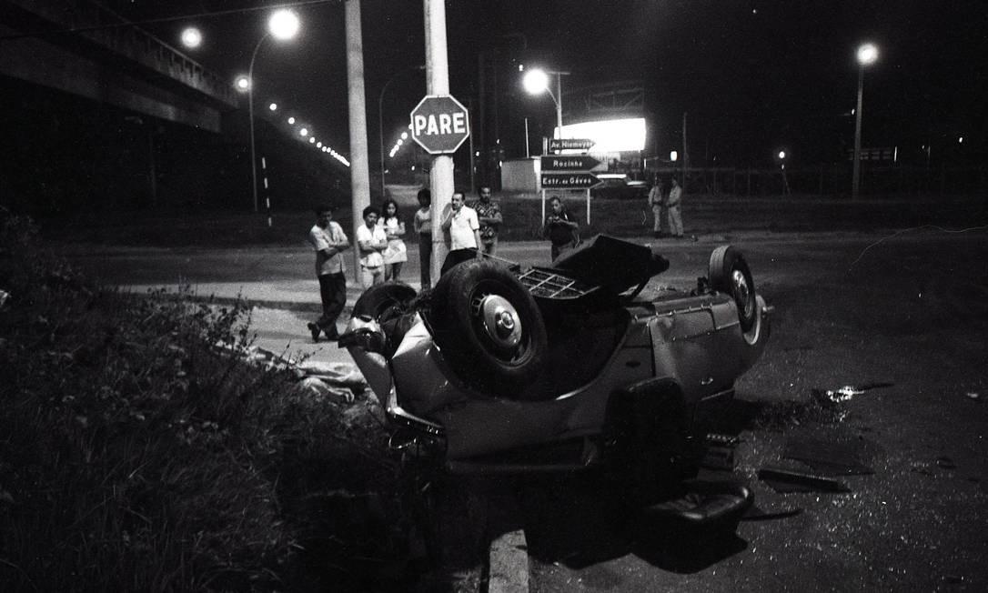 Coronel Perdigão, de branco encostado na poste, na cena do acidente de Zuzu Angel Foto: Otávio Magalhães/14-04-1976 / O Globo