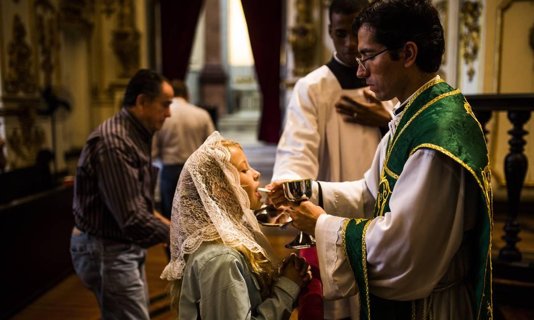 Jovem recebe hóstia de joelhos e usando um véu: grande parte das mulheres cobre a cabeça durante a missa Foto: Fabio Seixo
