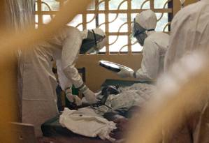 Médicos com equipamentos de proteção cuidam de pacientes de Ebola no centro de gerenciamento de casos em Monrovia, na Libéria Foto: HANDOUT / REUTERS