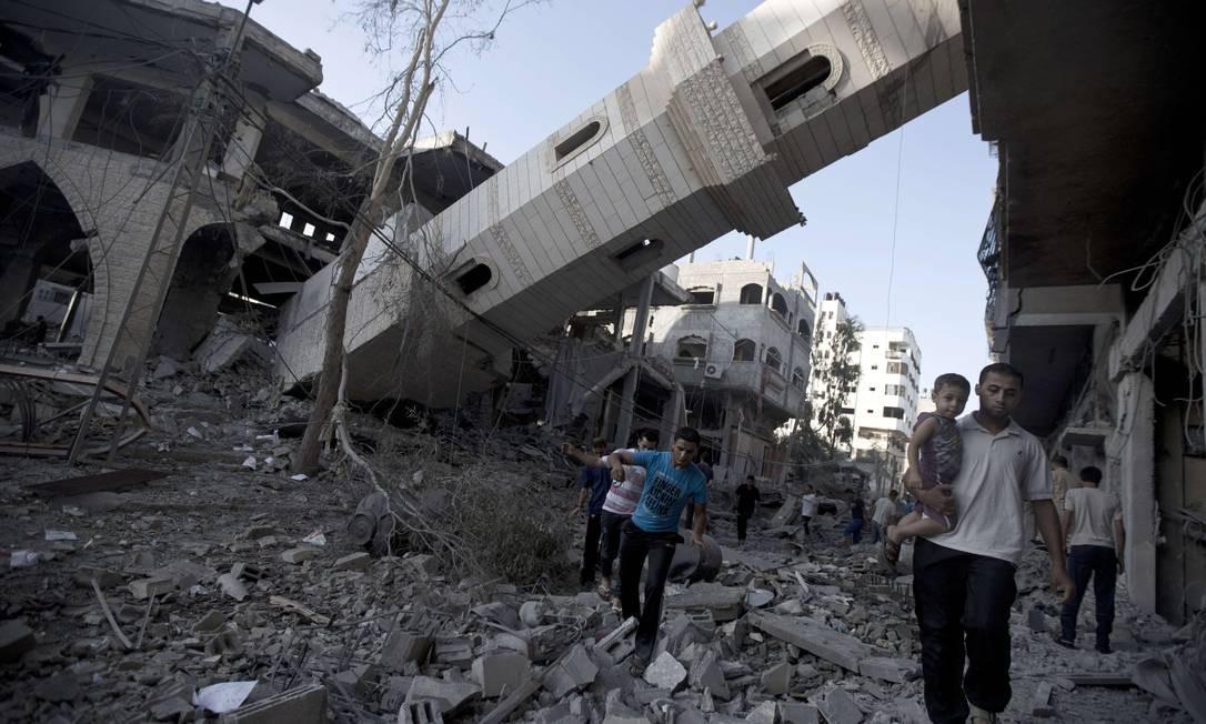 Palestinos caminham em frente a um minarete que desabou de uma mesquita na cidade de Gaza depois de ter sido atingida por um ataque israelense Foto: MAHMUD HAMS / AFP