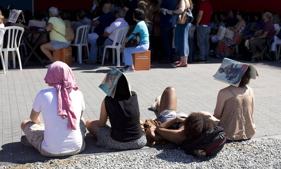 """Como a Tenda dos Aurores """"encolheu"""" e apenas uma parte é coberta, a maioria das pessoas fica no sol ao assitir aos debates e se protege como pode Foto: Márcia Foletto / Agência O Globo"""