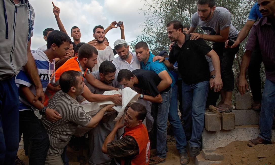 Uma família enterra um parente após um ataque de foguete, na Faixa de Gaza Foto: THE WASHINGTON POST