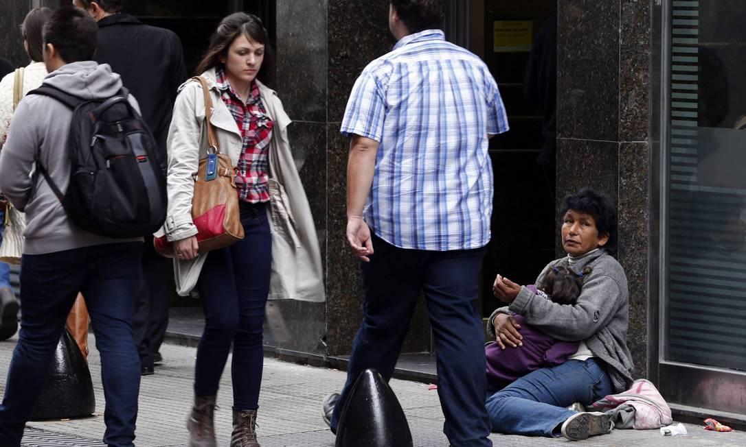 Na carne. Uma mulher com criança no colo pede esmolas no Centro de Buenos Aires: população vai sentir o calote Foto: Marcos Brindicci / Reuters