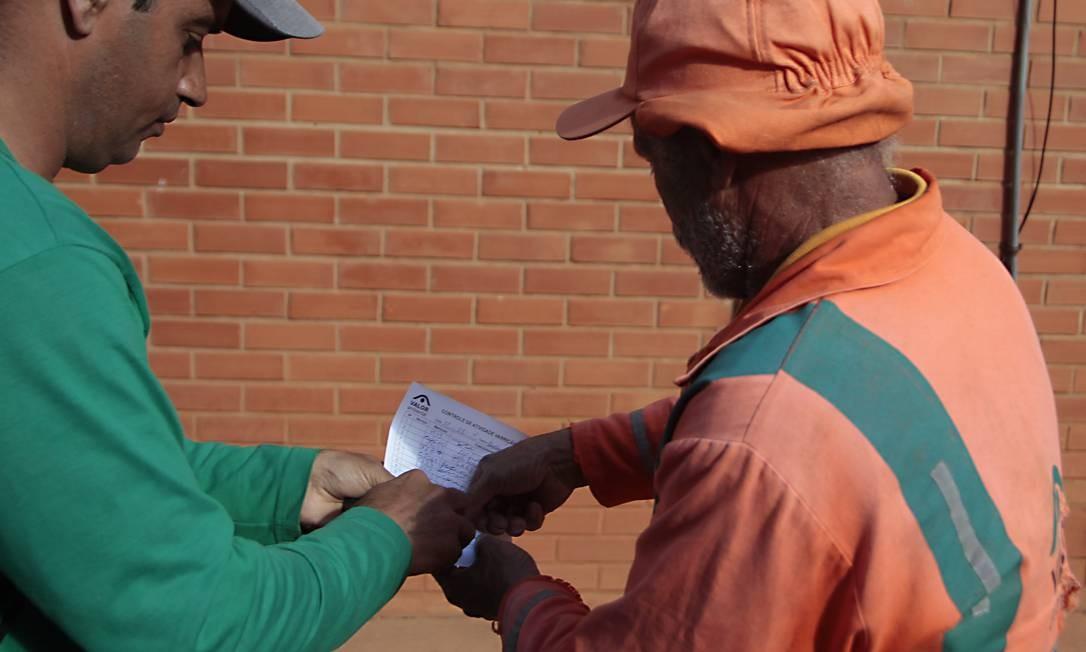 Francisco Cândido de Souza, que não sabe ler e escrever, assina o ponto com o polegar Foto: O GLOBO / Jorge William