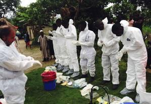 Voluntários se preparam para remover corpos suspeitos de terem contraído o vírus ebola Foto: HANDOUT / REUTERS