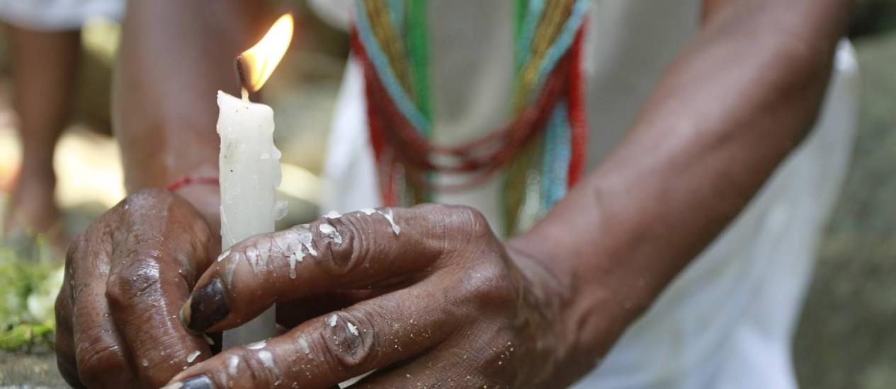 Devoção atacada: na imagem, adepta da umbanda acende vela em reverância a orixás. Culto às entidades africanas é associado ao demônio em vídeos na web Foto: Domingos Peixoto / Agência O Globo