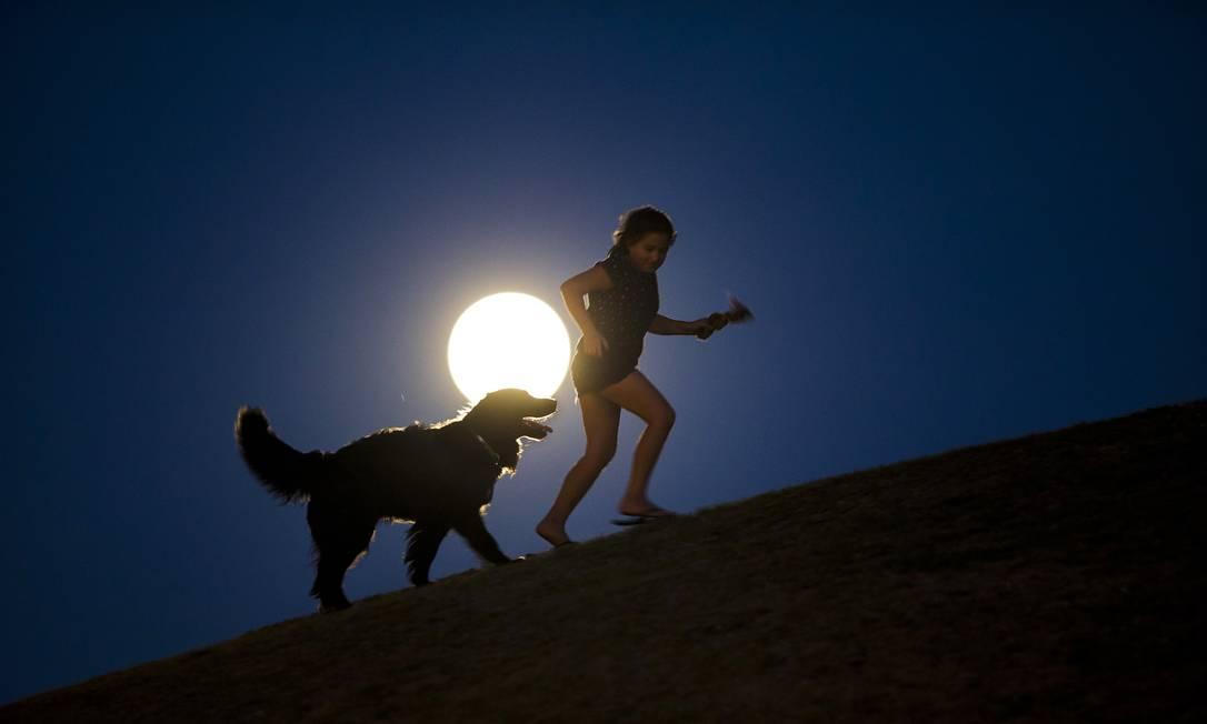 Em Madri, garota brinca com seu cachorro com a superlua ao fundo Andres Kudacki / AP