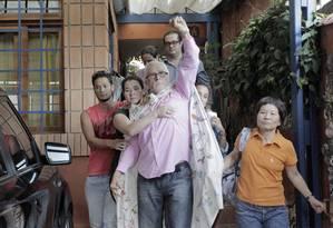 """Em 2013, Genoino, acompanhado da família, se veste com uma """"capa"""" para deixar sua residência, em São Paulo, e cumprir pena em Brasília Foto: Eliaria Andrade 15/11/2013 / O Globo"""