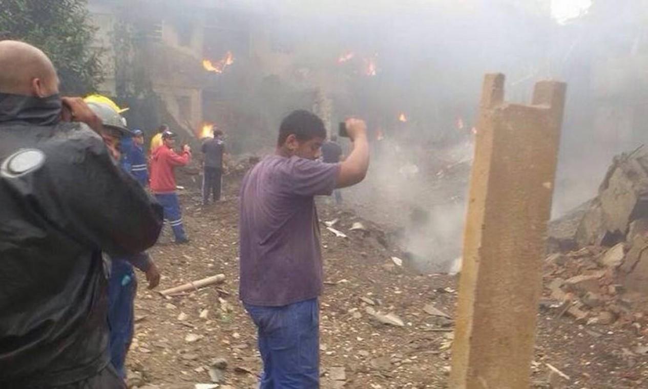 Pessoas observam prédios em chamas logo após a queda da aeronava Foto: @obviouziall/ Twitter