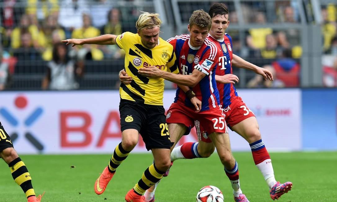 Thomas Müller, do Bayern, disputa jogada com Schmelzer. Campeão mundial com a Alemanha, meia não teve vida fácil na partida Foto: Patrik Stollarz / AFP