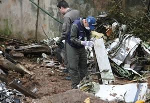 Peritos examinam pedaços da aeronave do candidato à presidência da República Eduardo Campos Foto: Michel Filho / Agência O Globo