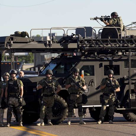 Policiais, com um atirador de elite no alto de um blindado, em Ferguson, Missouri Foto: WHITNEY CURTIS / NYT