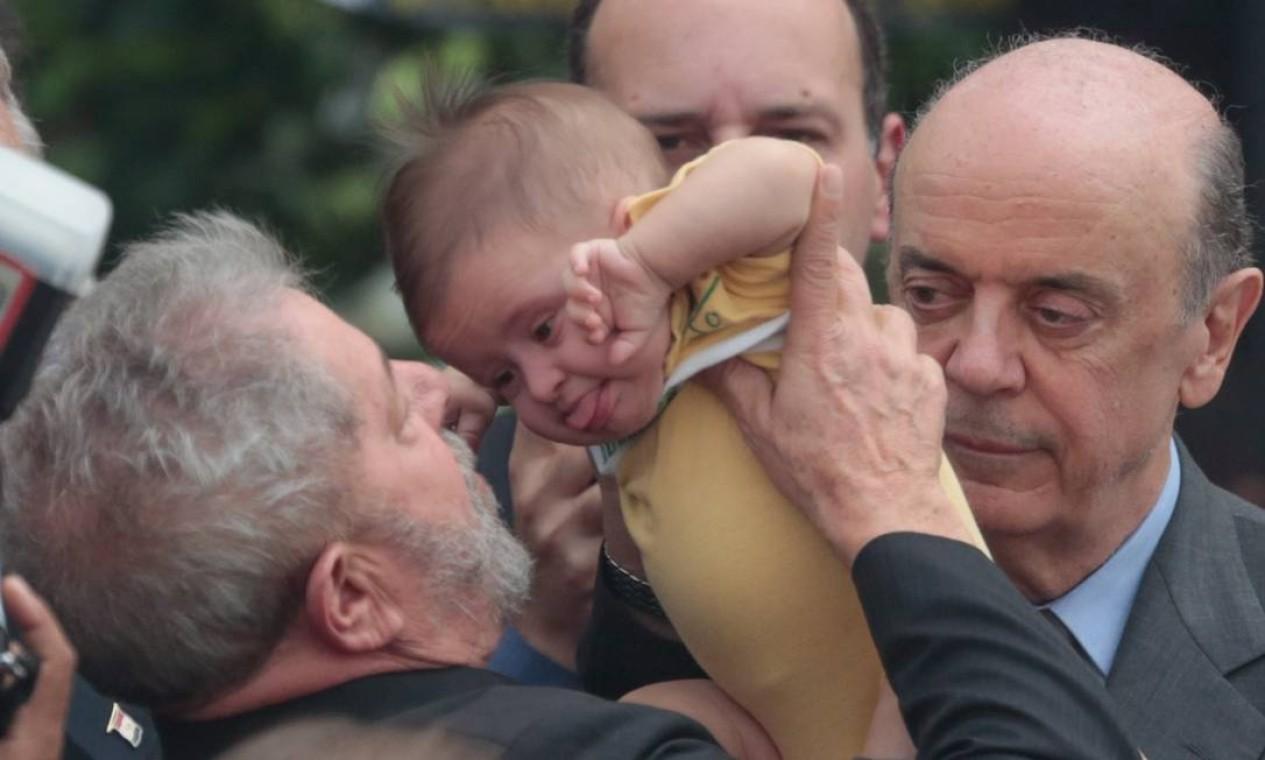 Renata entrega o filho Miguel ao ex-presidente Lula, que é observado por José Serra Foto: Pedro Kirilos / Agência O Globo