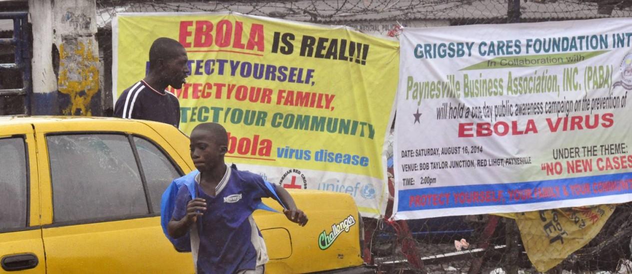 Cartazes alertam população de Monróvia que ebola é real. Na madrugada deste domingo, homens armados invadiram um centro de quarentena na capital da Libéria Foto: Abbas Dulleh / AP