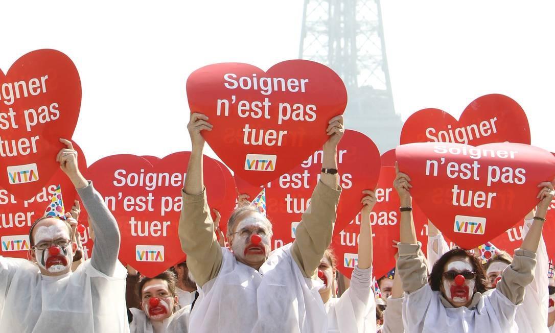 """Mobilização. Pessoas participam em frente à Torre Eiffel, em Paris, de um evento organizado pela """"Alliance VITA"""", que se colocou contra a eutanásia. No cartaz: """"Cuidar não é matar"""" Foto: KENZO TRIBOUILLARD / AFP PHOTO"""