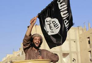 Militante jihadista agita bandeira do Estado Islâmico durante desfile em Raqqa. Senador americano John McCain defende que ataques aéreos sejam intensificados e levados à Síria, onde jihadistas mantêm controle sob parte do território Foto: REUTERS