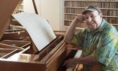 Donato sentado ao piano de madeira curupixá, vinda do Acre, que está em uma das salas de sua casa, na Urca Foto: Leo Martins