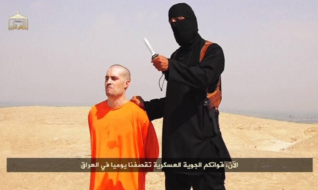 Militante mascarado do Estado Islâmico segura homem que seria o jornalista americano James Foley, pouco antes de decapitá-lo. Grupo enviou mensagem ao governo americano afirmando que outro jornalista pode ser morto Foto: REUTERS TV / Reuters