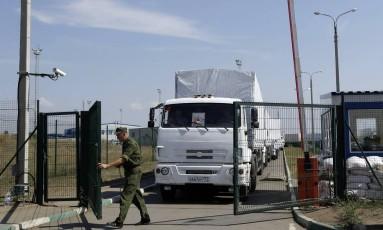 Um guarda de fronteira russo abre um portão para entrada dos primeiros caminhões russos com ajuda humanitária na Ucrânia Foto: Sergei Grits / AP